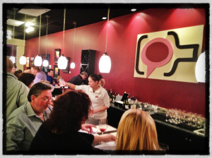 Owner Cortney Casey pours wine at the Michigan By The Bottle Tasting Room