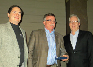 """Steve Zeller presents the award for """"Best Cold Climate White Wine"""" to Paul Quast and Peter Hemstad of St. Croix Winery"""
