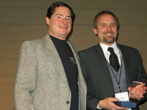 """Steve Zeller or Parley Lake Winery presents the """"People's Choice"""" award to Irv Geary of Wild Mountain Winery"""