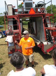 Todd    vineyard manager of Fenn Valley Winey, explains his BEI mechanical grape harvester to guests of the winery's