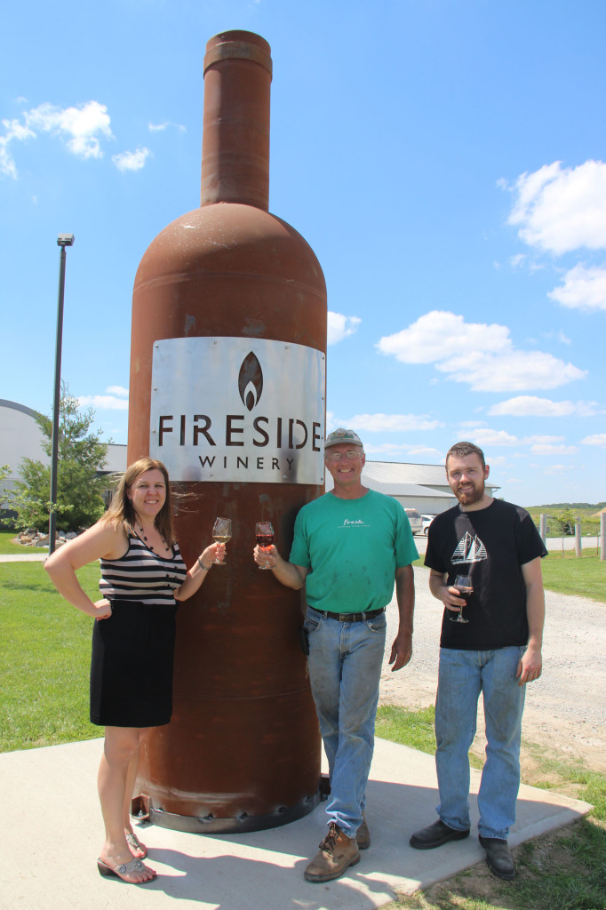 Cassie Bott, Randy Schnebbe and Peter Miller of Fireside Winery next to the Midwest's biggest wine bottle.