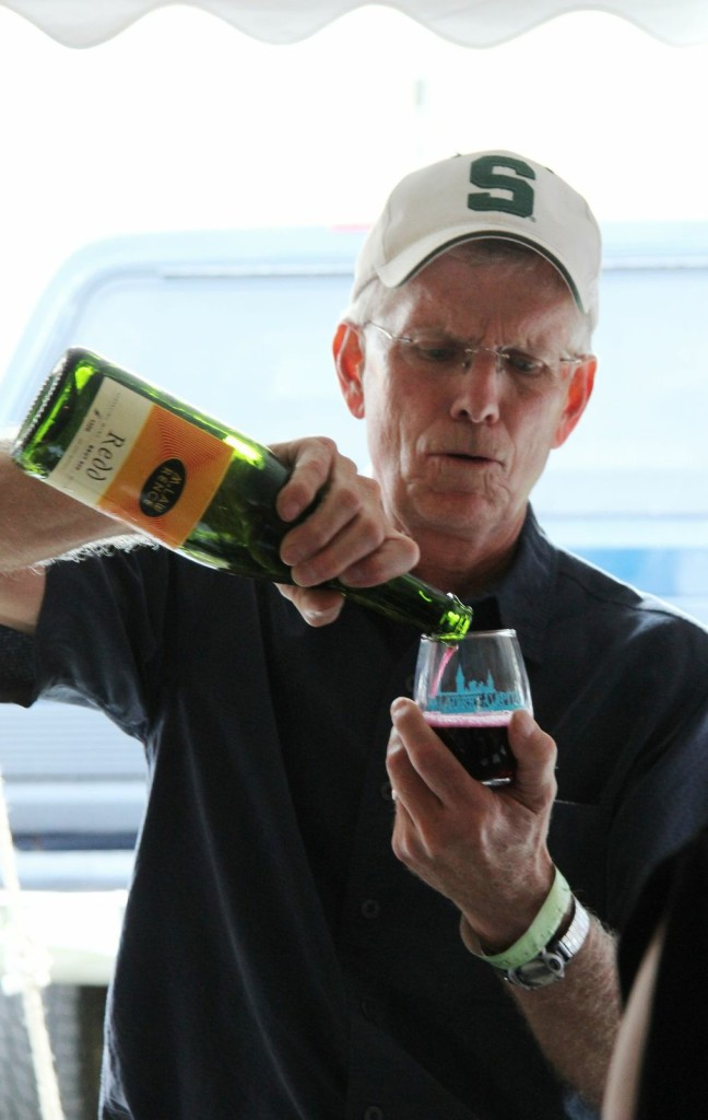 A festival volunteer–one of 300 volunteers who worked between the Friday night Winemaker's Party and Saturday's main festival–pours the popular L. Mawby Vineyards' popular Redd, a Brut wine made from Regent and Marechal Foch grapes hand picked, crushed, fermented on the skins and pressed. .