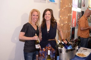 Darcy Morowitz and Kelly Kniewel pouring Michigan wine at an art exhibition.