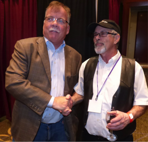Two infamous Minnesota vineyard and winery owners Paul Quast from Saint Croix Vineyards and Don Millner from Millner Heritage Vineyard and Winery shake hands for a photo opp.